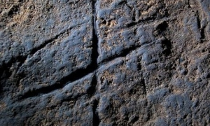 Deep graven lines enhanced with colored clay decorate a Neanderthal cave.  Is this the work of a prehistoric Miro?